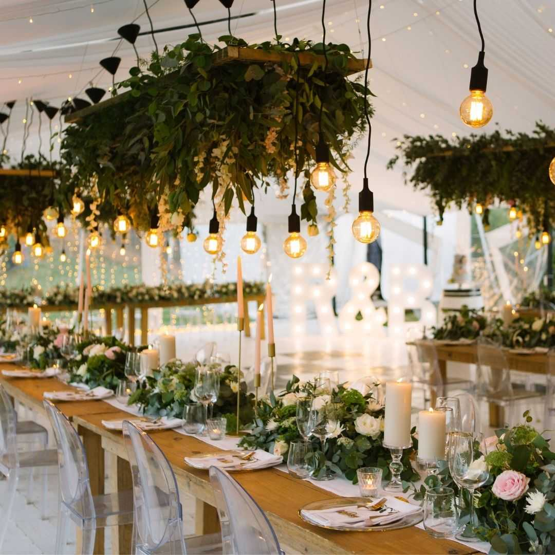 rustic wedding tent decor with hanging bulbs and wooden tables