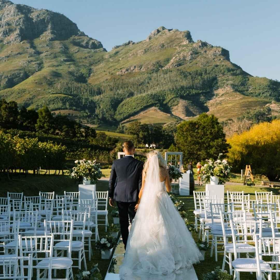 bride and groom walking across wedding aisle
